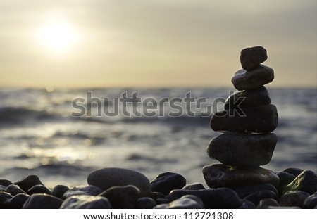 Stack of stones on beach. Sea, sun and sky.