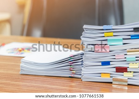 Stack of student's homework that assigned to students to be completed outside class on teacher's desk separated by colored paper clips. Document stacks arranged by various colored paper clips on desk. ストックフォト ©