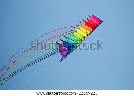 Stack of 12 stunt kites in rainbow colours on a blue sky background