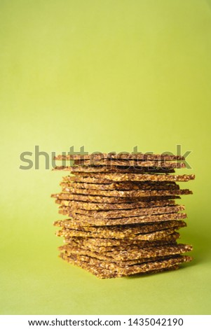 Stack of super-Useful rye multi-grain whole-grain crackers with different seeds on a green background with space for text. superfoods healthy organic products.