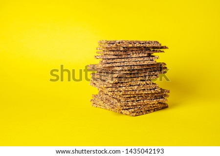 Stack of super-Useful rye multi-grain whole-grain crackers with different seeds on a yellow background with space for text. superfoods healthy organic products.
