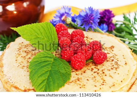 stack of tasty pancakes with berries and leaves of raspberries, bright blue cornflowers