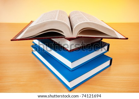 Stack of text books against gradient background