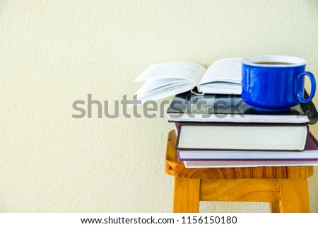 Stack of textbooks notepads workbooks blue cup of hot tea on high wooden stool on white wall background. University college education homeschooling learning concept. Authentic lifestyle image #1156150180