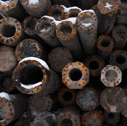 Stack of the concrete poles (posts, bollards) with rusty metal reinforcement. Construction material.