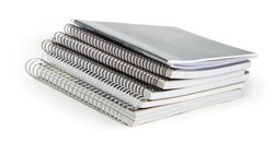 Stack of the different exercise books with wire spiral binding at selective focus on a white background