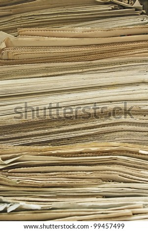 Stack of the old yellowed newspapers close up