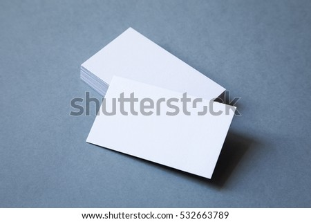 Stack of thick blank business cards on a grey background, top view. The top card is shifted to front. #532663789