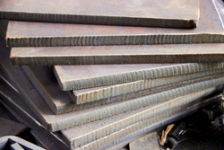stack of thick metal sheets cut on a plasma cutting machine