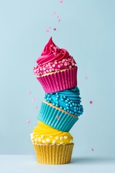 Stack of three colorful cupcakes with falling sprinkles