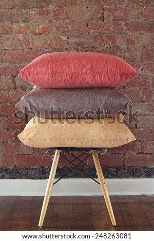 Stack of three linen cushions on chair brick wall background