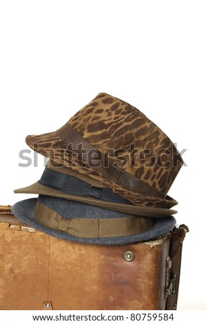 Stack of three mens hats on Antique suitcase