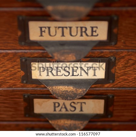 "Stack of three old, oak flat file drawers with ""PAST"", PRESENT, and ""FUTURE"" printed on tags in tarnished brass label holders. Shallow depth of field with focus on ""PRESENT""."