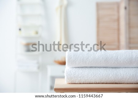 Stack of towels on table against blurred background