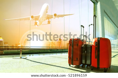 stack of traveling luggage in airport terminal building and passenger plane flying over urban scene  #521896159