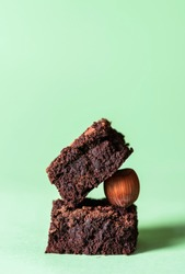 Stack of two dark chocolate brownies and a hazelnut, on a mint green background. Delicious fudge chocolate cake squares. A cute pile of brownies.