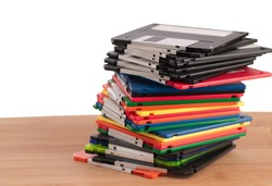 Stack of Used Floppy Diskettes Sitting on Wood Surface with Room for Text