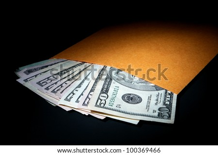 Stack of used large denomination US dollar bills sticking out of a plain manila brown envelope as a metaphor for under the table cash bribery and illegal hush money corruption in dramatic light