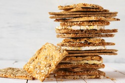 Stack of various crispy wheat, rye and corn flatbread crackers with sesame and sunflower seeds on white wooden background.