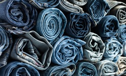 Stack of various shades blue jeans. Jeans stacked isolated on white background. Blue denim jeans texture banner with copy space for text design background. Canvas denim fashion texture