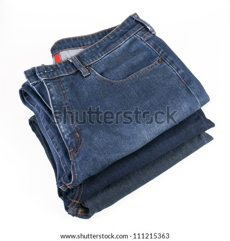 Stack of various shades of folded blue jeans on a white background