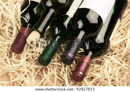 Stack of various wine bottles lying on straw.