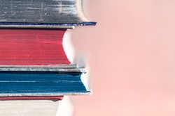 Stack of vintage books in detail and large copy space with pastel pink background/Retro Book Pile