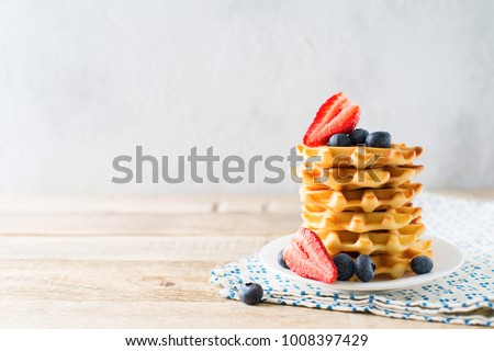 Stack of waffles with blueberries and strawberries on grey background, copy space