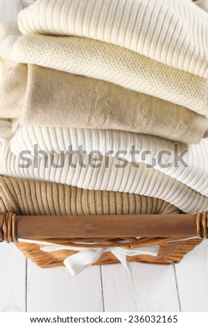 Stack of warm sweaters in basket on white wood. #236032165