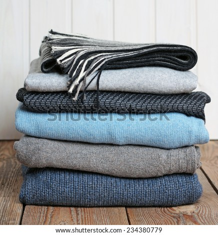 Stack of warm woolen clothing lying on a wooden table