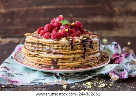 Stack of wheat golden pancakes or pancake cake with freshly picked raspberry, chopped pistachios, chocolate sauce on a dessert plate