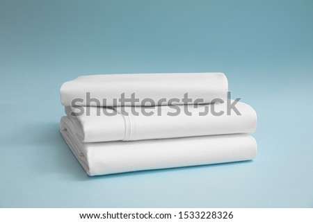 Photo of  Stack of white bedding against blue backdrop, folded soft bed clothes, stack of white cotton sheets on a blue background for advertising, commercial and mock up