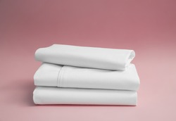 Stack of white bedding against pink backdrop, folded soft bed clothes, stack of white cotton sheets on a pink background for advertising, commercial and mock up