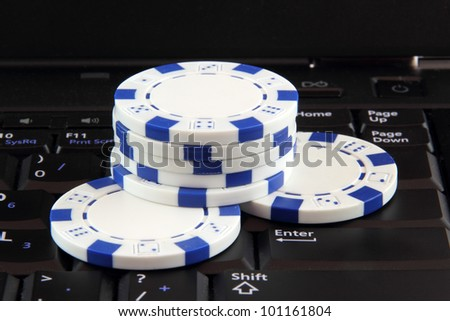 stack of white casino gambling chips on keyboard, online gaming concept