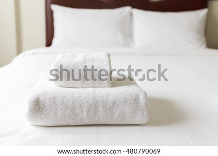 Stack of white cleaning folded tower on the bed #480790069