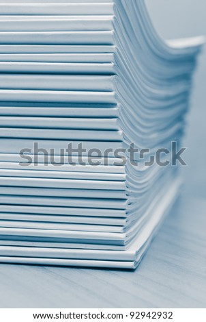 Stack of white journals on table, closeup blue toned