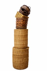 Stack of wicker straw osier handmade baskets different size and pattern at isolated white background for home storage