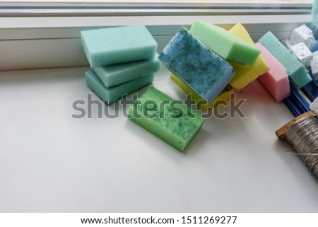 Stack of wispes, chalk and coil with thread on windowsill in classroom