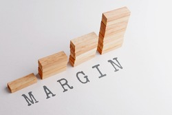 Stack of wood block in statistics graph shape with text MARGIN. Business concept in rising and growing margins. Selective focus, gray background.