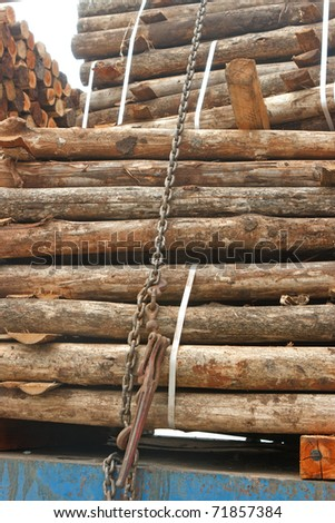 Stack of wood on truck, tied down with chain and steel strips