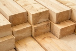Stack of wooden squared beams for construction. Material for the construction of a wooden building. Closeup big wooden boards