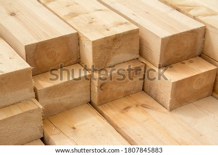 Photo of  Stack of wooden squared beams for construction. Material for the construction of a wooden building. Closeup big wooden boards