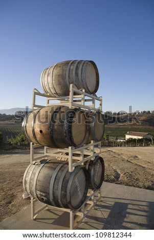 Stack of wooden wine barrels on stand with house in the background