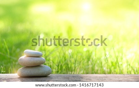 Stack of zen stones on abstract nature green summer background. Relax still life with stacked of stone. zen pebble stones, spa wellness tranquil scene, soul equanimity calmness concept. copy space