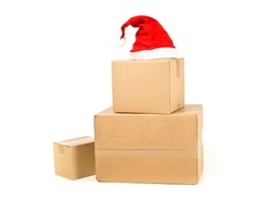 Stack or heap of brown carton cardboard boxes with red santa hat over white background, christmas shopping or online ordering concept