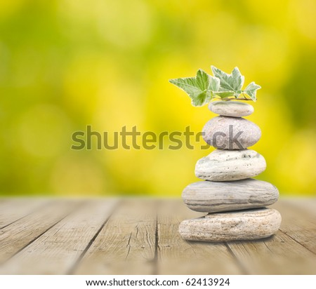 Stack pebbles on wooden table with green background