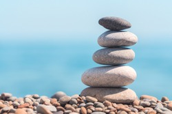 Stack stones on the coast of the sea in the nature. Cairn on the ocean beach, five pebbles tower. Concept of balance and harmony. Calm and spirit