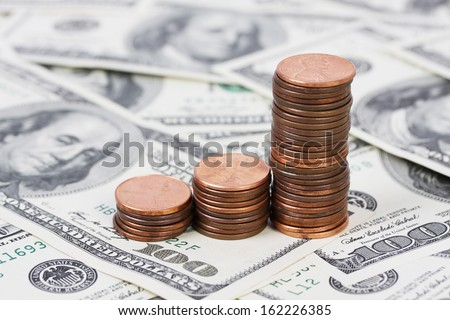 Stack US pennies in an ascending bar graph on background of money american hundred dollar bills