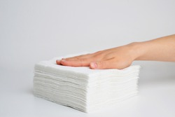 Stack white napkins in hand on white background isolation. Paper napkins with female hand. Stack of clean paper napkins.