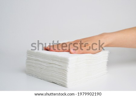 Stack white napkins in hand on white background isolation. Paper napkins with female hand. Stack of clean paper napkins. Stok fotoğraf ©